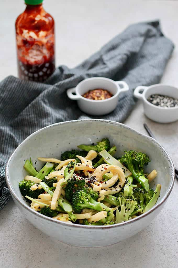 Pan fried broccoli and ribbons of egg sprinkled with sesame seeds in a blue bowl