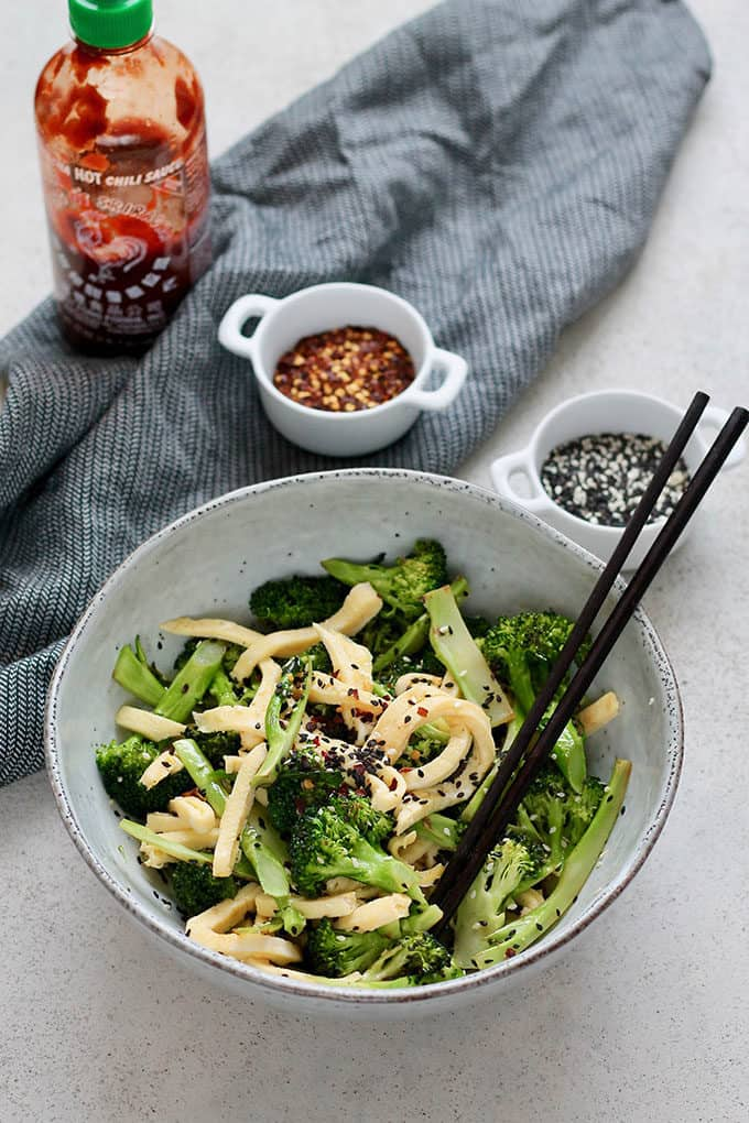 a blue bowl with pan-fried broccoli and egg with a pair of black chopsticks and a black tea towel