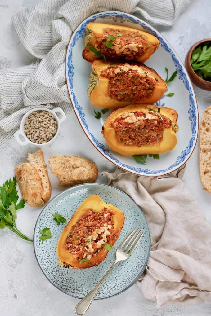 overhead photo with slices of stuffed acorn squash on a blue platter