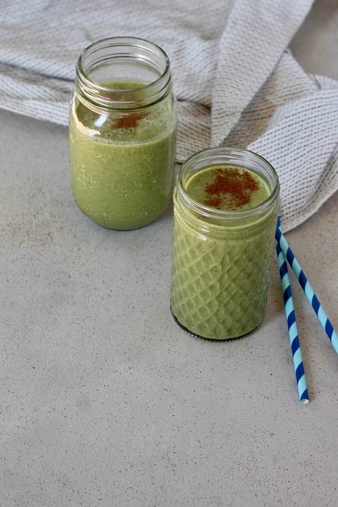 Two green smoothies on a grey background with two blue straws
