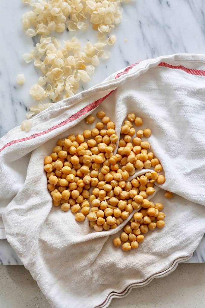 peeled chickpeas on a white tea towel with chickpea skins to the side