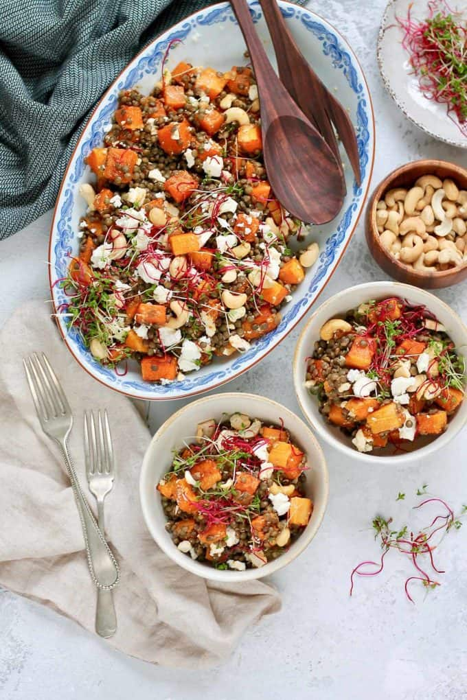 two bowls of roasted butternut squash salad with lentils and topped with cashews and microgreens