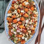 overhead photo of roasted butternut squash salad with lentils on a blue platter