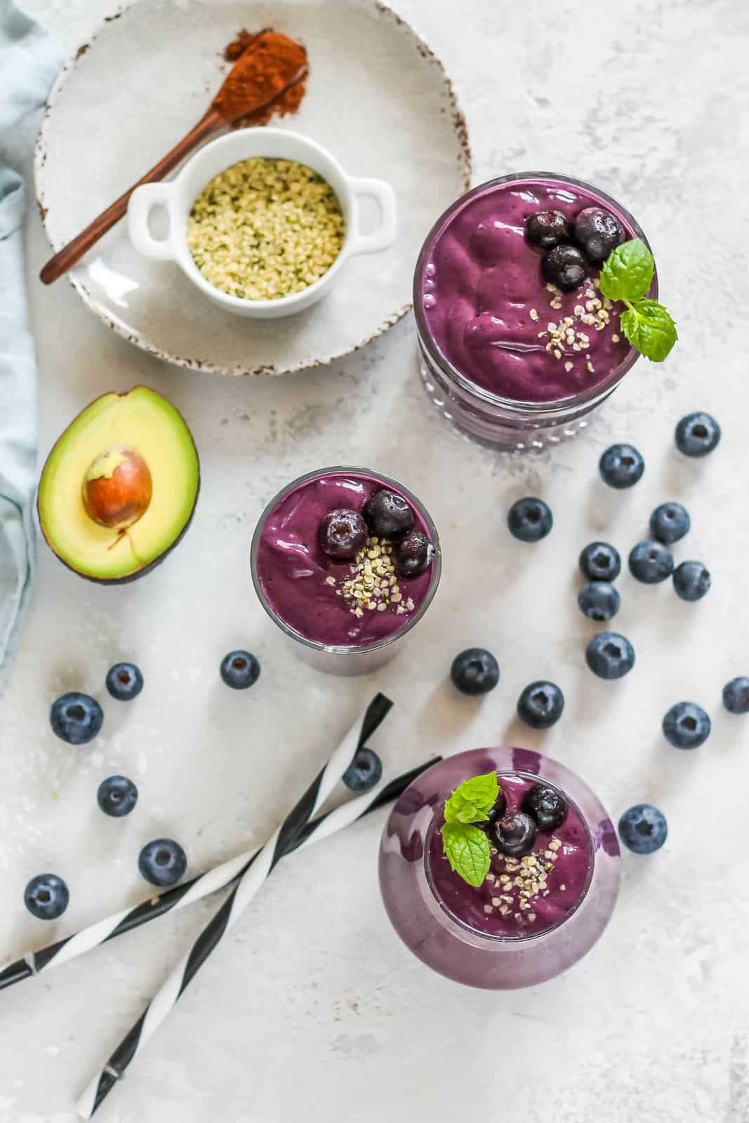 overhead photo with three glasses of blueberry smoothie on a grey background. There are blueberries and avocado scattered around.