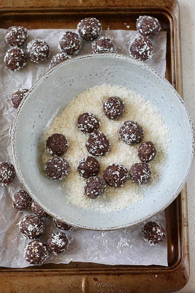 a bowl of coconut with chocolate energy balls being rolled in it
