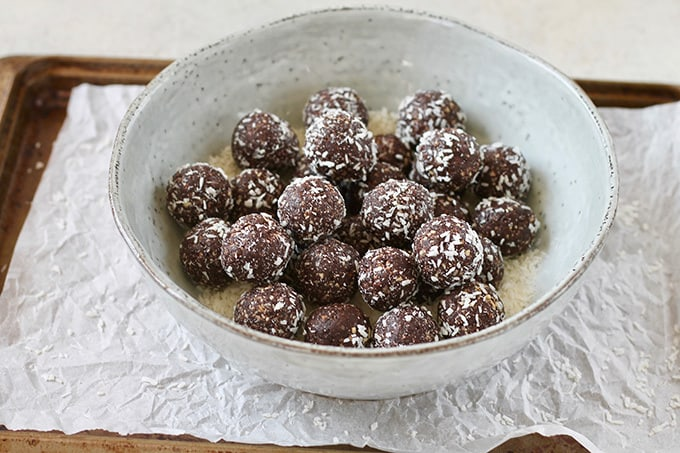 A large blue bowl filled with chocolate energy balls with dates