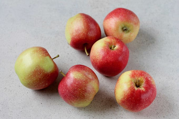 six red apples on a grey background