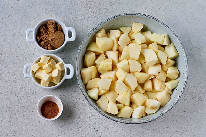 cinnamon, butter, and brown sugar beside a bowl of peeled and chopped apples
