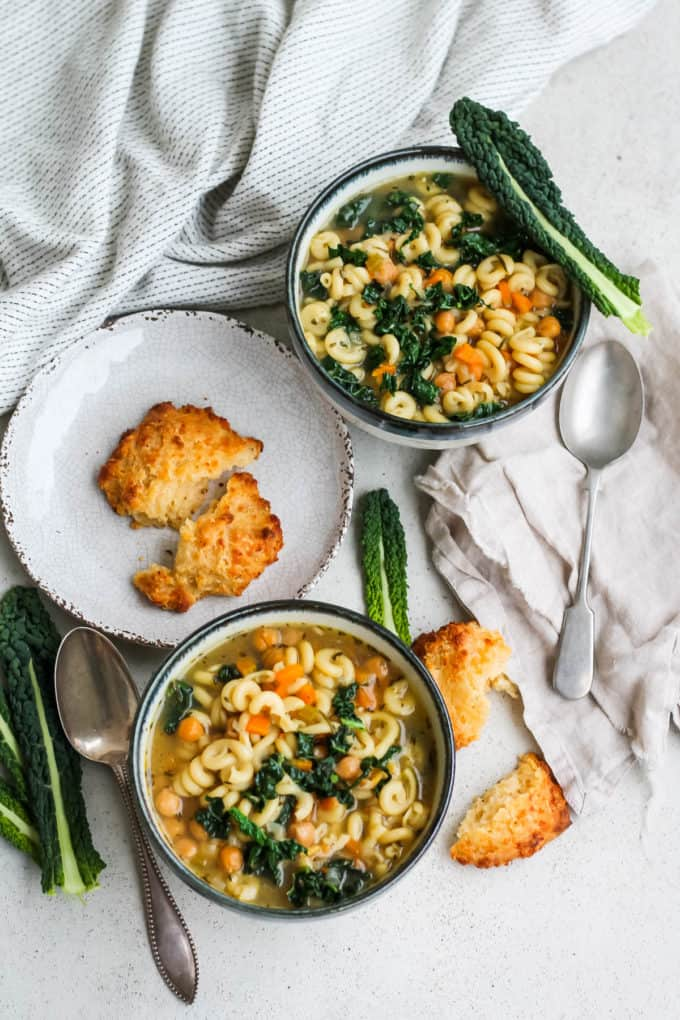 overhead photo of two bowls of chickpea noodle soup on a grey background with leaves of kale scattered around