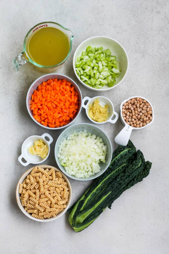 chickpeas, pasta, kale, celery, carrots, onion, garlic, ginger, and broth on a grey background
