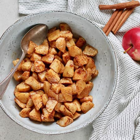 a bowl of roasted apples with a silver spoon tucked in the side