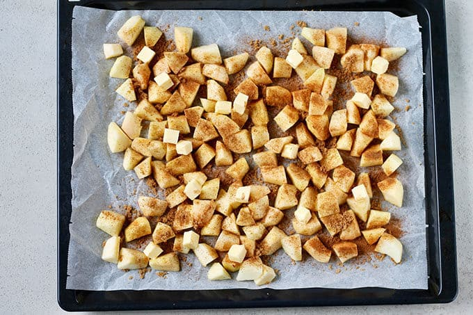 a tray of chopped apples sprinkled with cinnamon and sugar