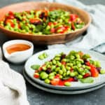 edamame bean salad on a blue plate with a white tea towel to the side