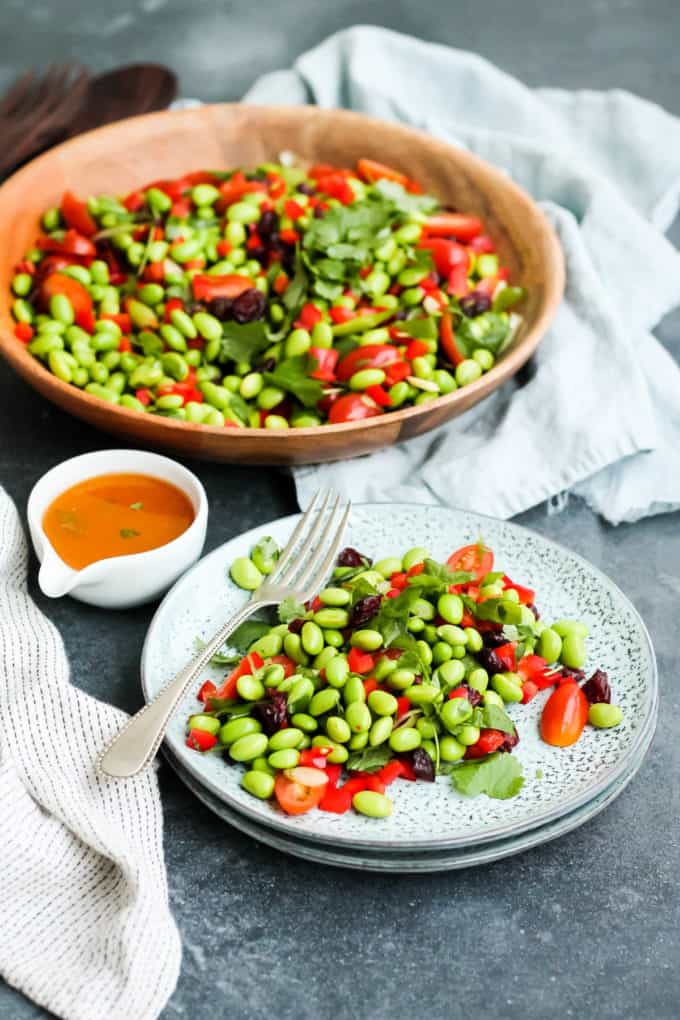 a plate of edamame bean salad with a large bowl of salad in the background