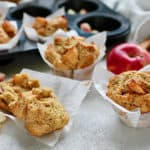 a whole wheat muffin broken open in front of a tray of baked muffins with roasted apples