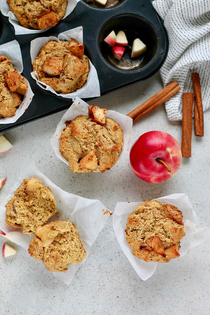 overhead photo of whole wheat muffins with roasted apples, with apple chunks and cinnamon sticks scattered on a grey background