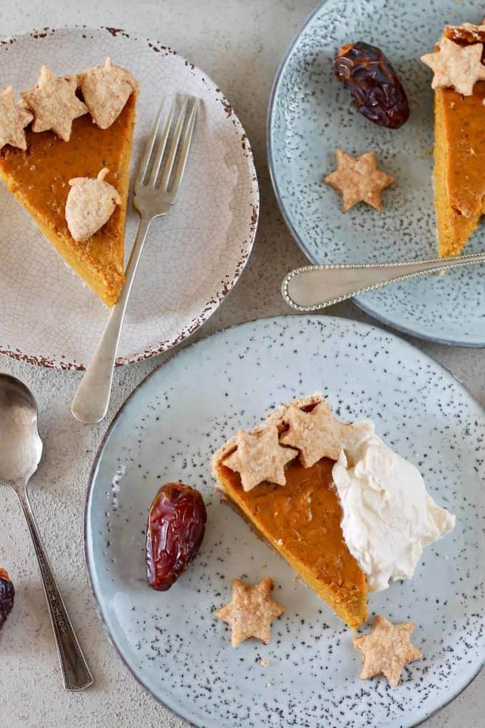 overhead photo of three slices of pumpkin pie on blue plates