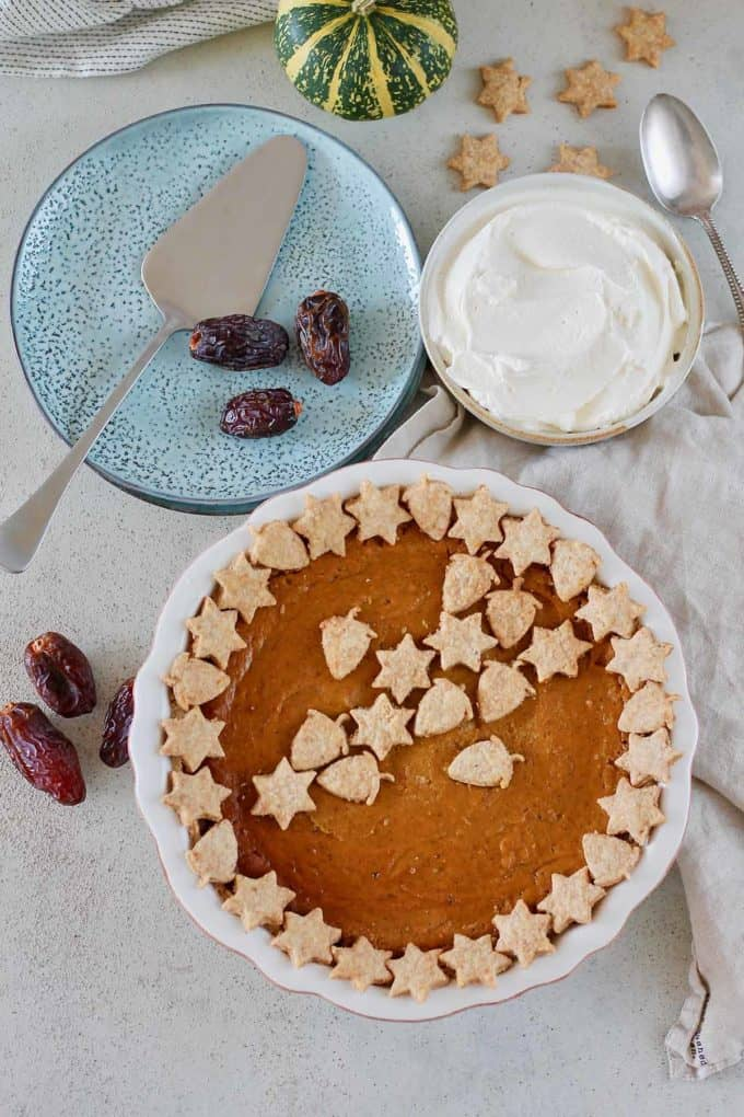 overhead photo of a refined sugar free pumpkin pie decorated with pastry cutouts