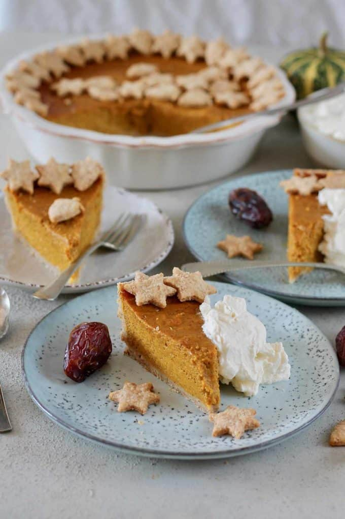 a slice of naturally sweetened pumpkin pie on a blue plate with a date and a scoop of whipped cream