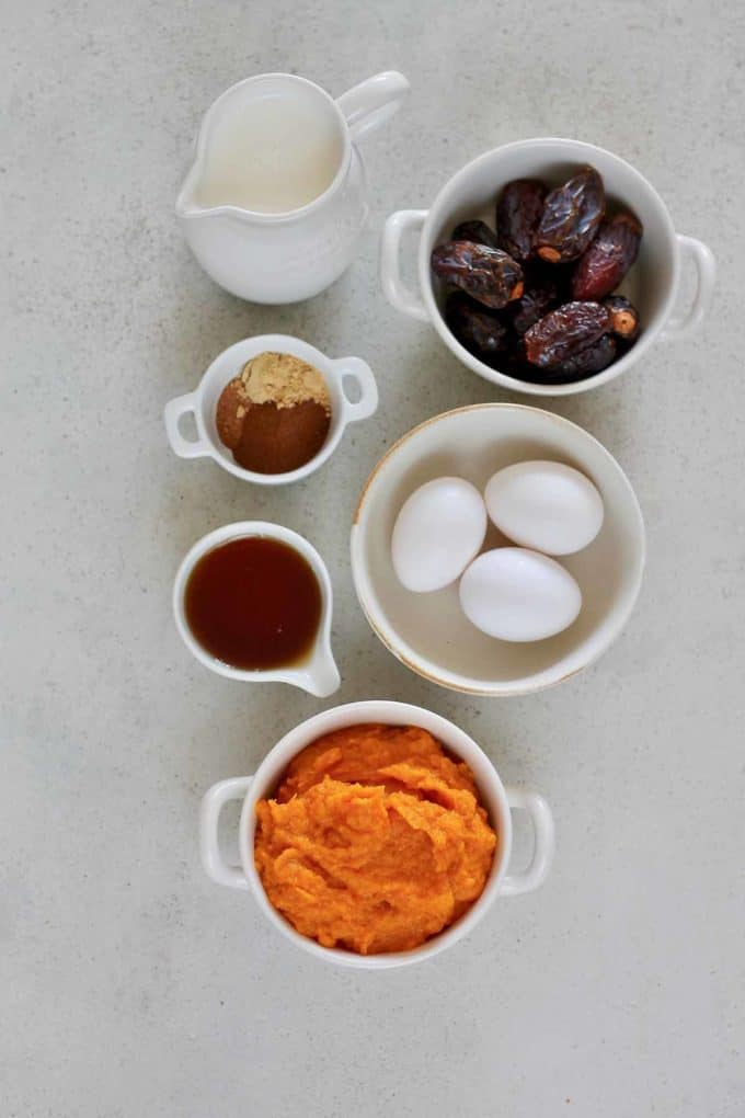 pumpkin puree, eggs, dates, milk, spices, and maple syrup on a grey background