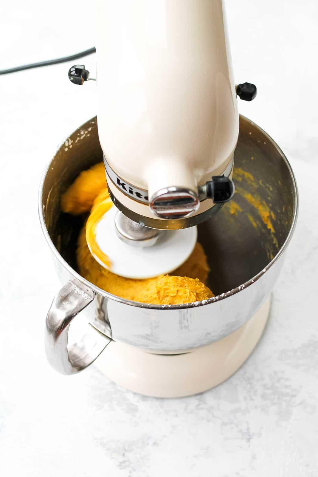 saffron dough being mixed in a white kitchen aid mixer