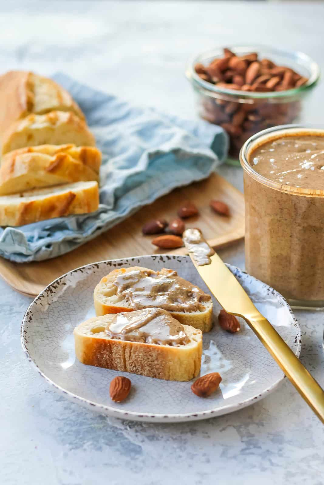 two slices of french bread spread with vanilla almond butter on a white plate with a gold knife on the side