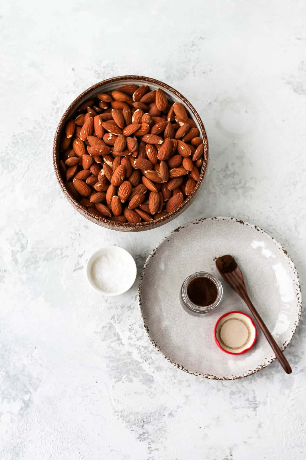 a bowl of almonds and a plate with a little jar of vanilla powder on a wooden spoon