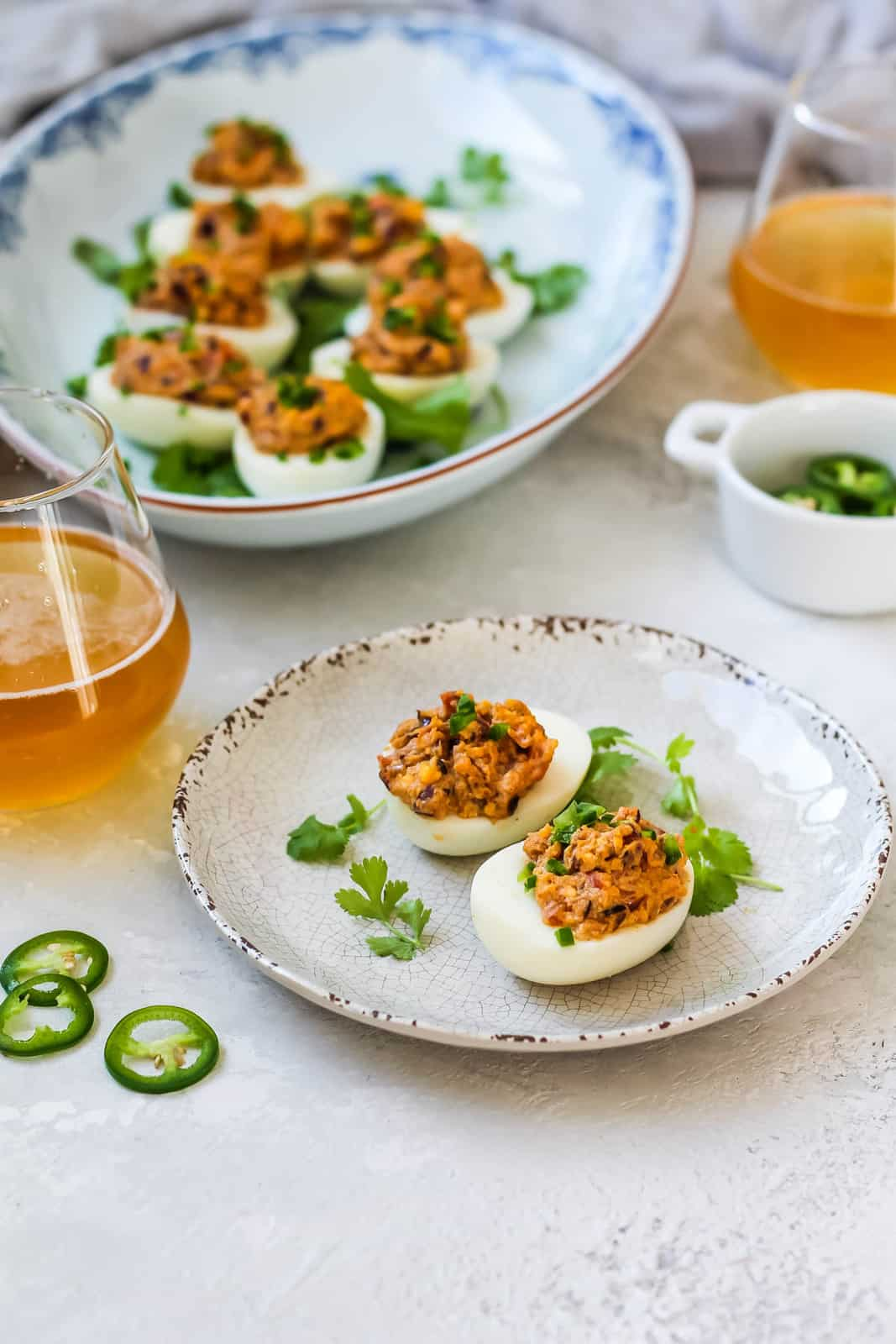 curried deviled eggs on a white plate with a platter of eggs in the background