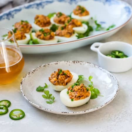 curried devilled eggs topped with jalapeno peppers on a white plate with a beer to the side