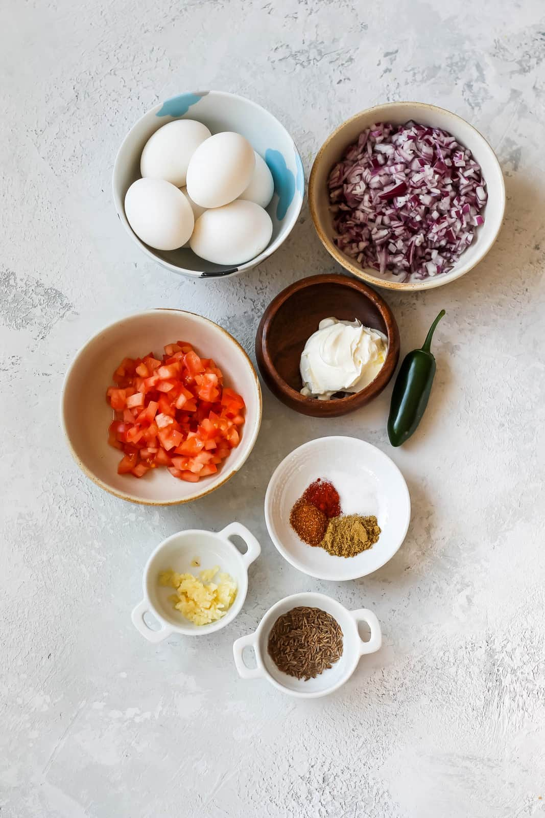 eggs, red onion, yogurt, tomatoes, spices, garlic, and jalapeno on a grey background