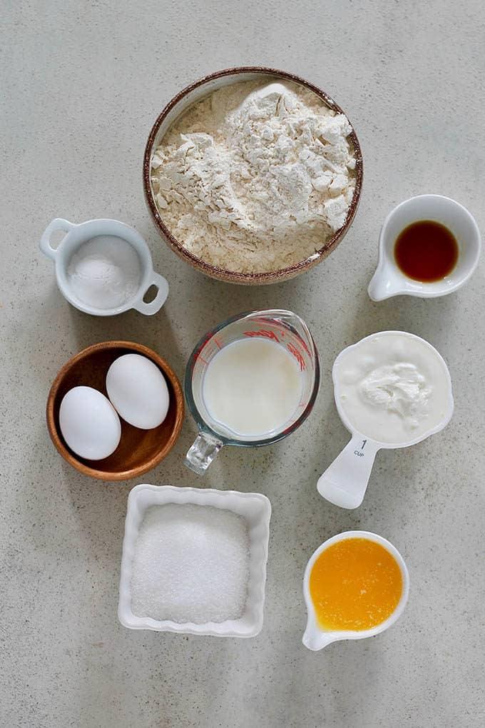 flour, eggs, butter, yogurt, vanilla, milk, baking powder, and sugar on a grey background