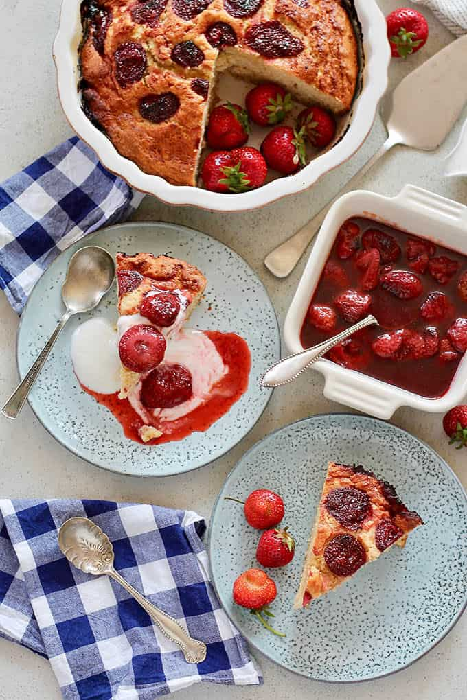 overhead photo of strawberry yogurt cake topped with roasted strawberries sauce