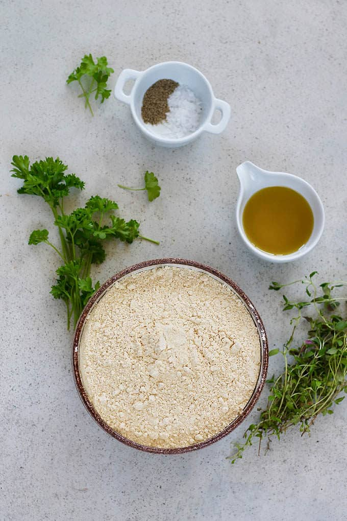 chickpea flour, herbs, salt, pepper, and olive oil on a grey background
