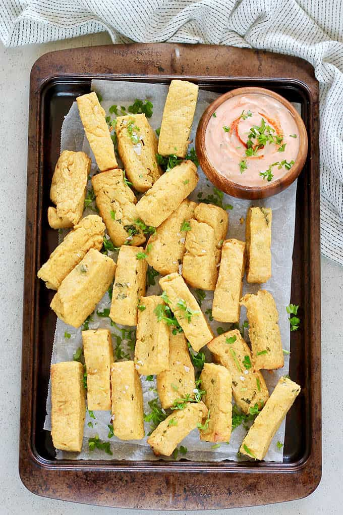 baked chickpea fries on a metal tray with a wooden bowl of dip