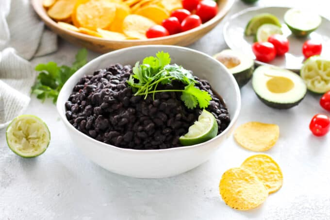 a white bowl of instant pot black beans with some sliced avocados and tomatoes in the background