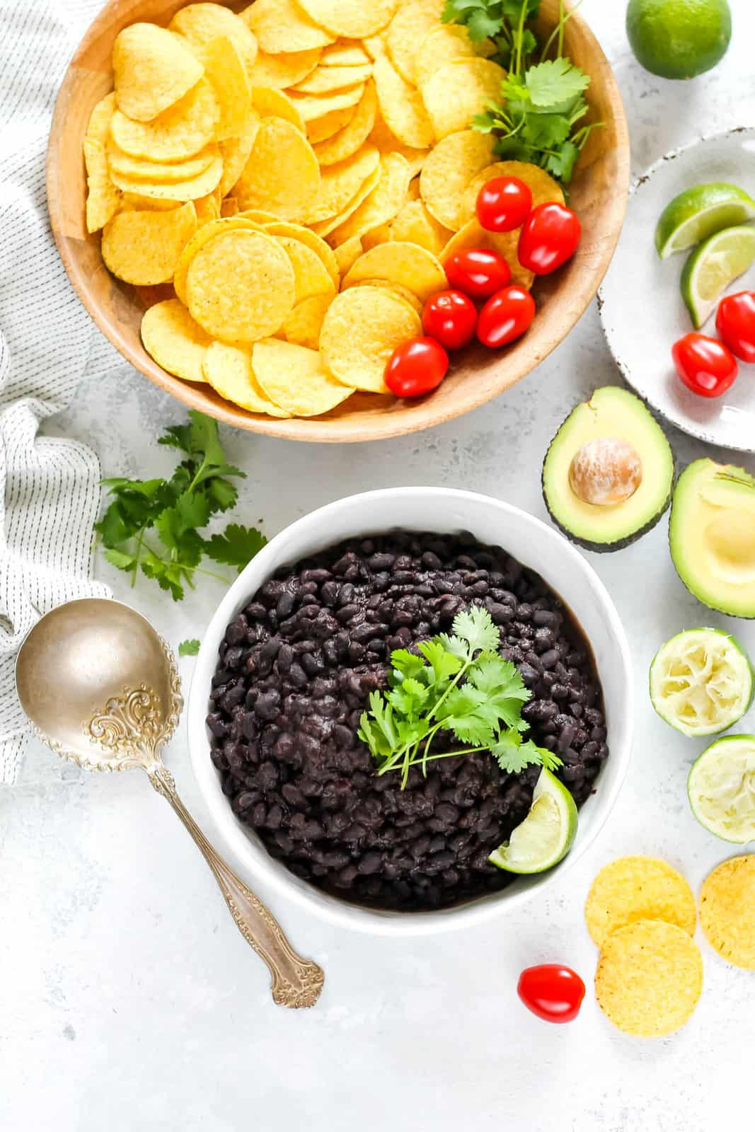 overhead photo of a white bowl filled with cooked black beans topped with cilantro. A bowl of nacho chips is in the background.
