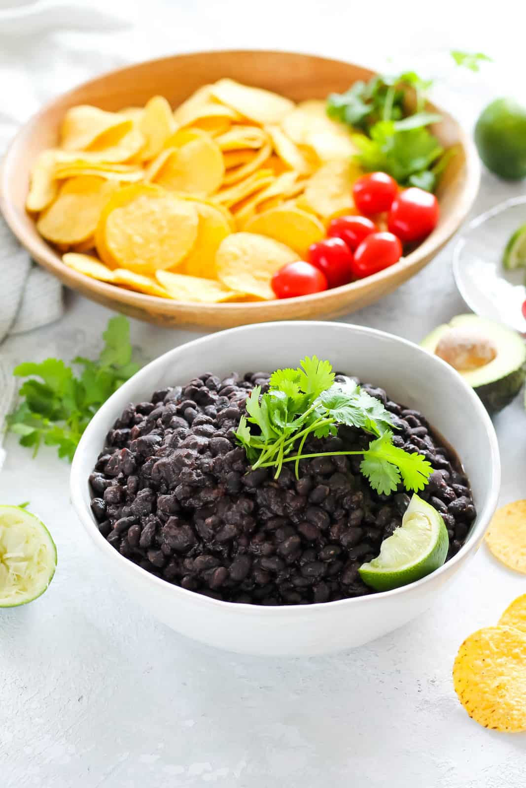 a white bowl filled with instant pot black beans topped with cilantro and a wedge of lime