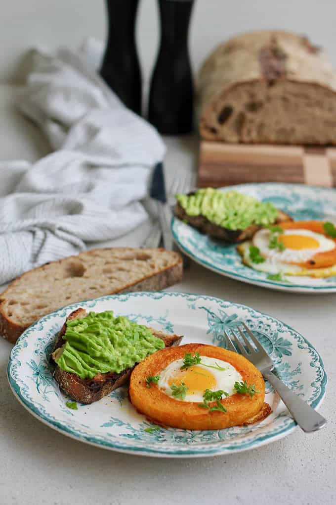 Landscape shot of baked egg-in-a-squash-hole on plates with avocado toast with bread and pepper mills in the background