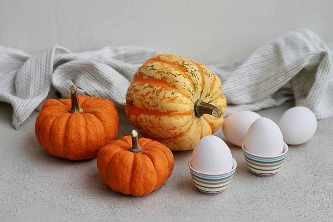 mini pumpkins, carnival squash, and eggs on a grey background