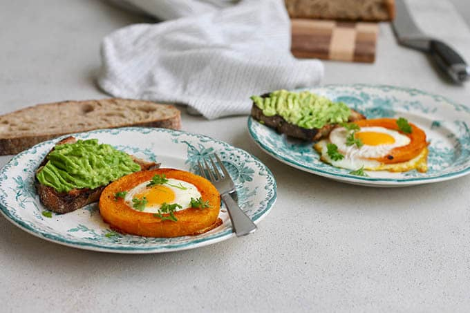 baked egg-in-a-squash-hole on plates with avocado toast