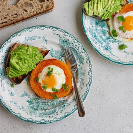 overhead shot of baked egg-in-a-squash-hole on plates with avocado toast
