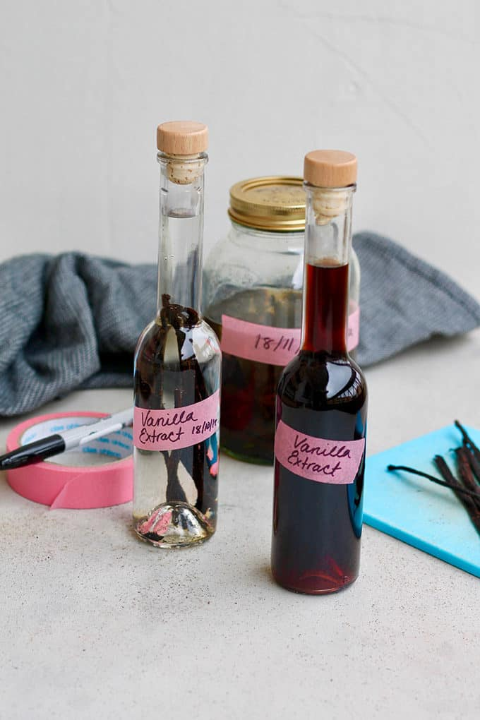 three bottles of homemade vanilla extract on a grey background