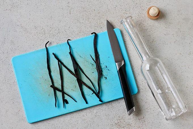 split vanilla beans on a blue cutting board