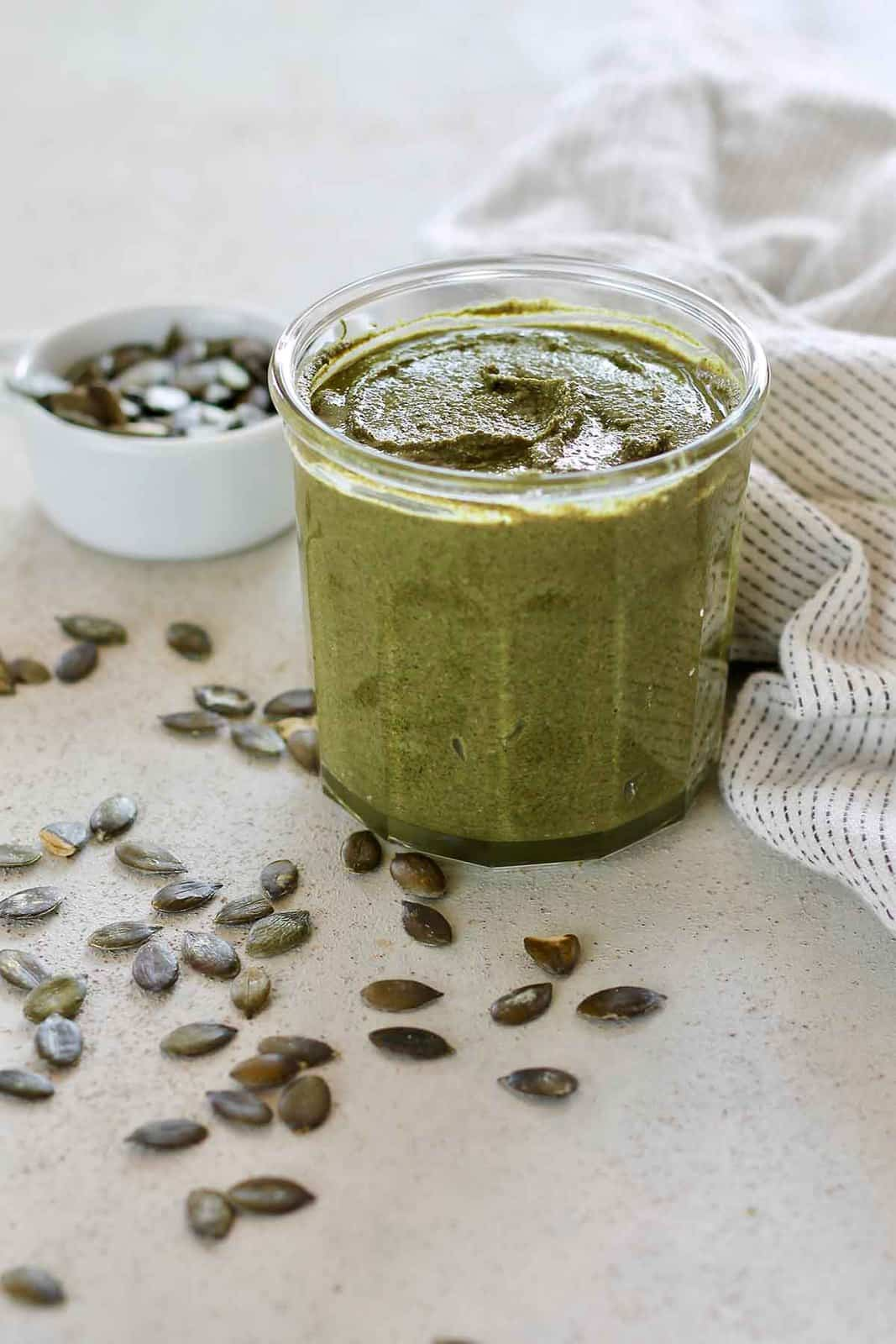 homemade pumpkin seed butter in a glass jar with pumpkin seeds scattered around