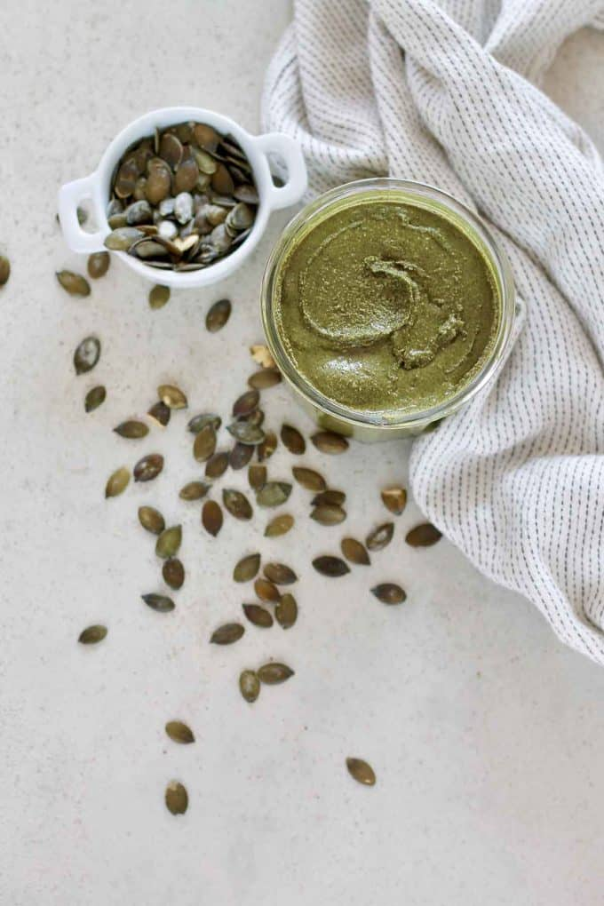 overhead photo of pumpkin seed butter on a grey surface