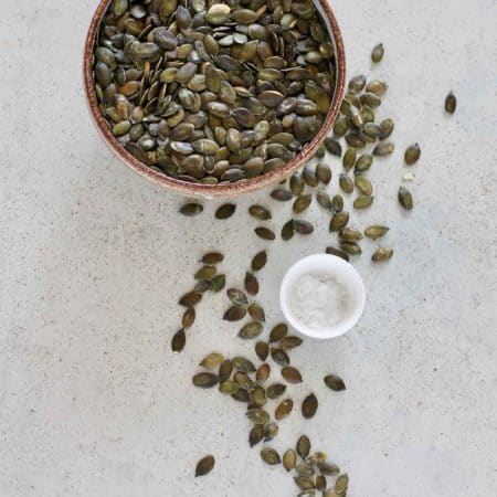 a bowl of pumpkin seeds on a grey surface beside a small bowl of sea salt