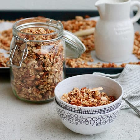 White patterned bowls with banana granola in front of a tray of freshly made granola