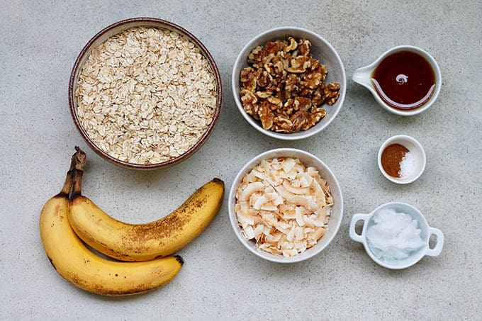 oats, bananas, walnuts, coconut chips, maple syrup, coconut oil, and cinnamon on a grey background