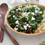 kale salad with cranberries in a wooden salad bowl with quinoa to the side