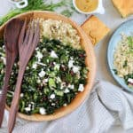 kale salad with cranberries, quinoa, and feta in a wooden salad bowl with wooden salad servers on top